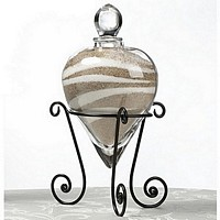 Heart shaped glass vase filled with white and tan colored sand resting in a black wire base