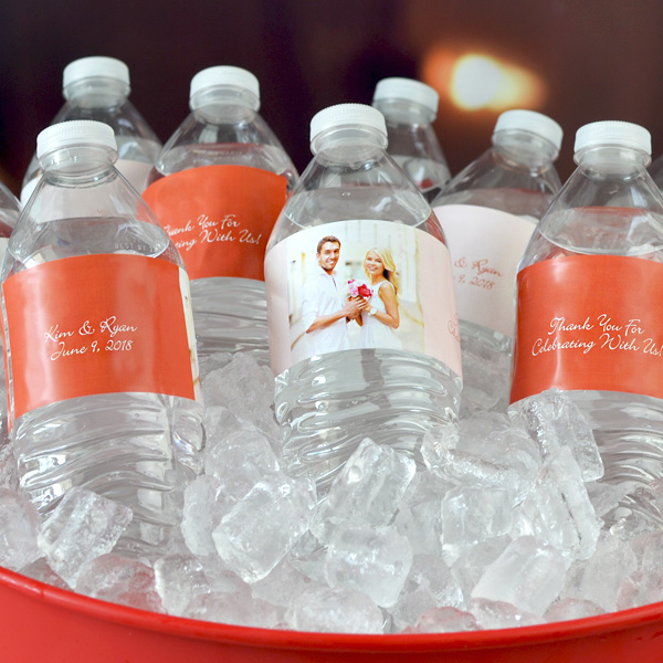Bottled water wrapped in personailzed water bottle labels custom printed with photo of bride and groom, bride and groom's name and wedding date with custom thank you message to guests.